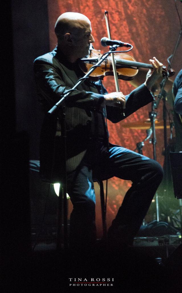 primo piano di lucio fabbri, seduto su uno sgabello, vestito di grigio, intento a suonare il violino