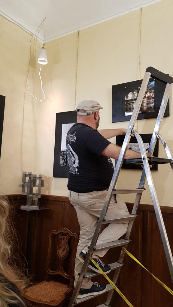 arte e medicina -  il dottor ravazzani su una scala di schiena con maglietta nera e pantaloni beige mentre mette un quadro ad una parete