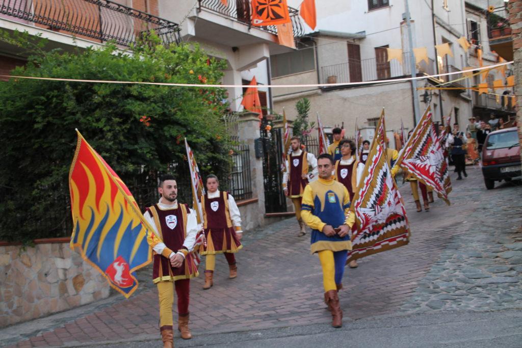 Gli sbandieratori del palio di Bisignao in corteo per le strade con le bandiere in mano