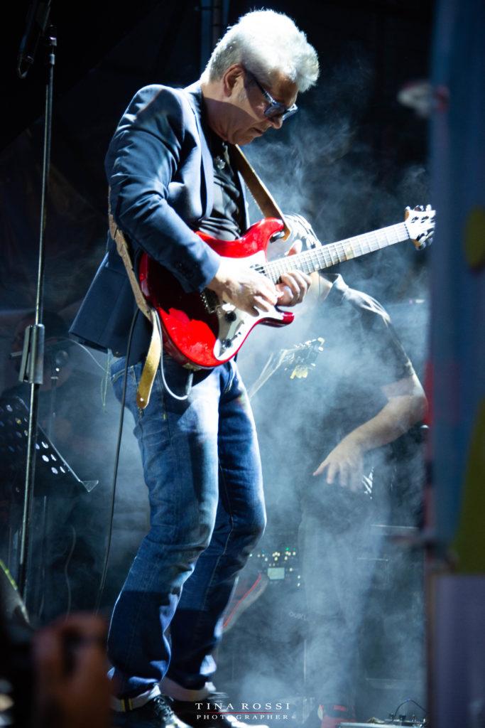Michele zarrillo - inpiedi, di profilo suona una chitarra rossa