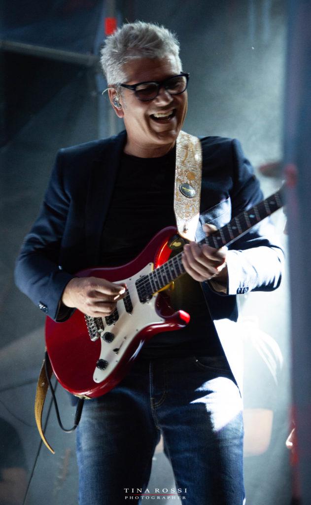 Vicere e rinascere tour - Michele Zarrillo sorridente con una chitarra rossa, suona al concerto del parco dora