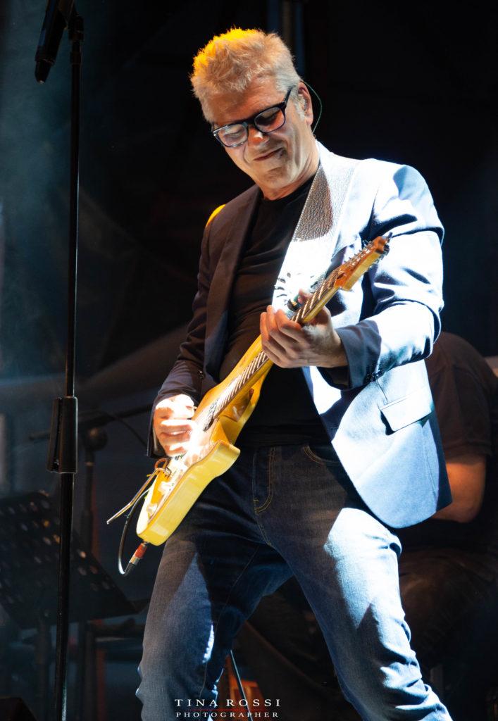 Michele Zarrillovestito con jeans e giacca scura suona una chitarra gialla sorridendo