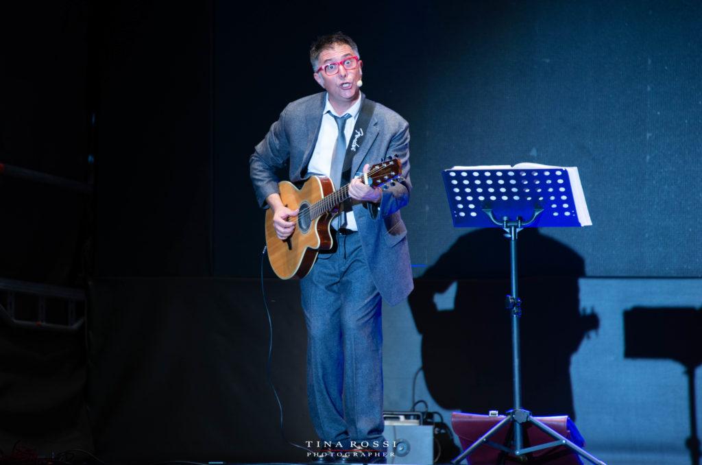 Cab41: Giancarolo Aiosa con giacca e cravatta suona la chitarra facendo una smorfia. Sulla destra un leggio