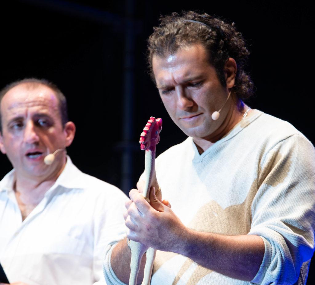 Marco Turano nell imitazione di Antonio Banderas tiene un pollo di gomma in mano e lo contempla assorto