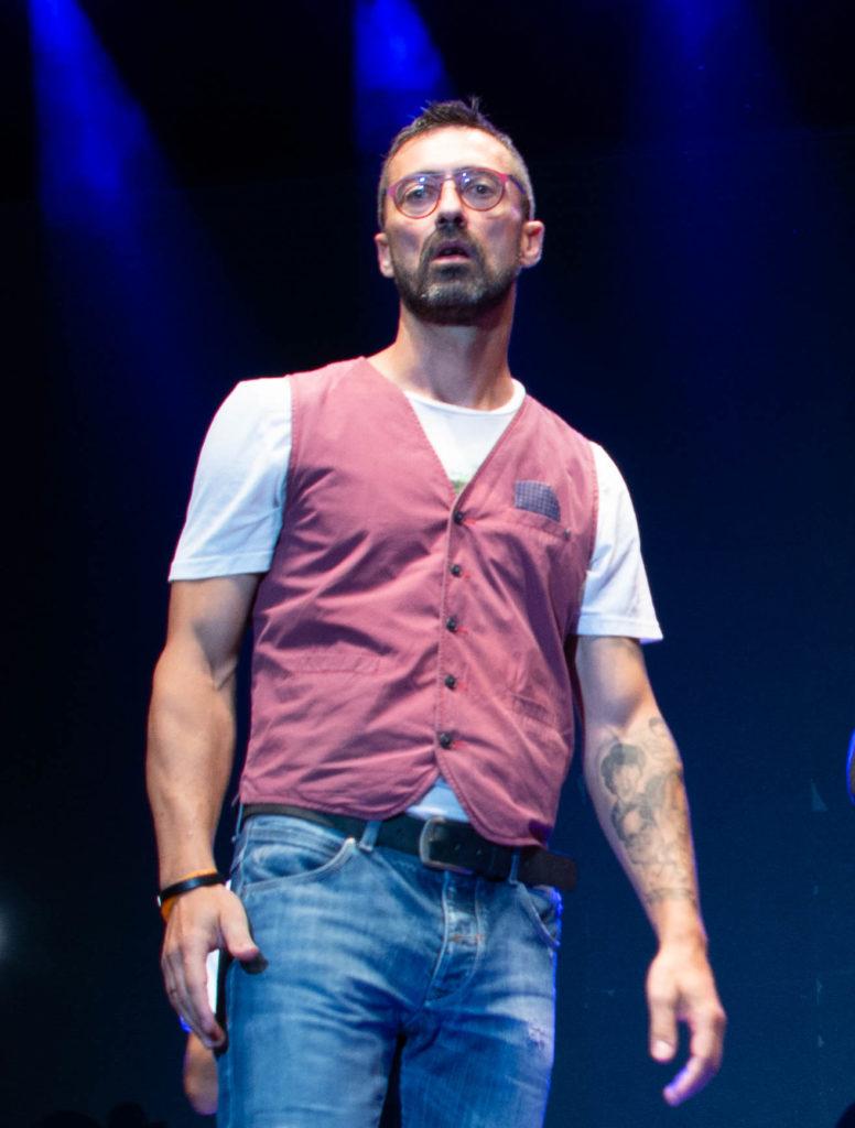 cab41 davide allena con t shirt bianca, gillet rosso e jeans guarda il pubblico con espressione sorpresa