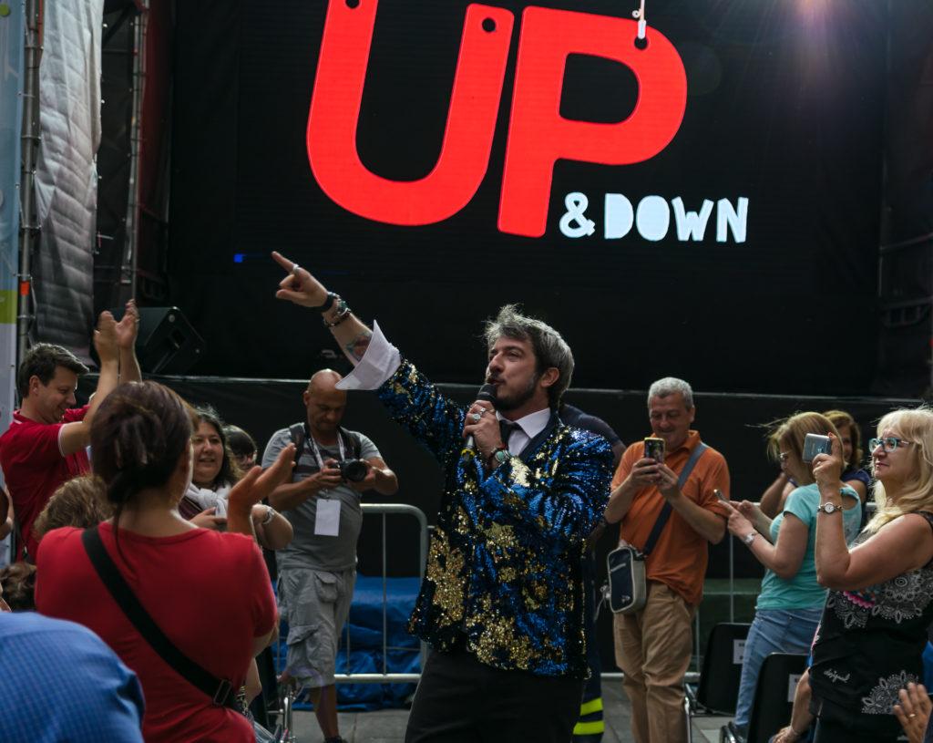 Paolo Ruffini indossa una giacca azzurra e dorata, in mezzo al pubblico indica il palco con il microfono in mano. intorno a lui delle persone che lo fotografano con il cellulare e dietro di lui la scritta up and down