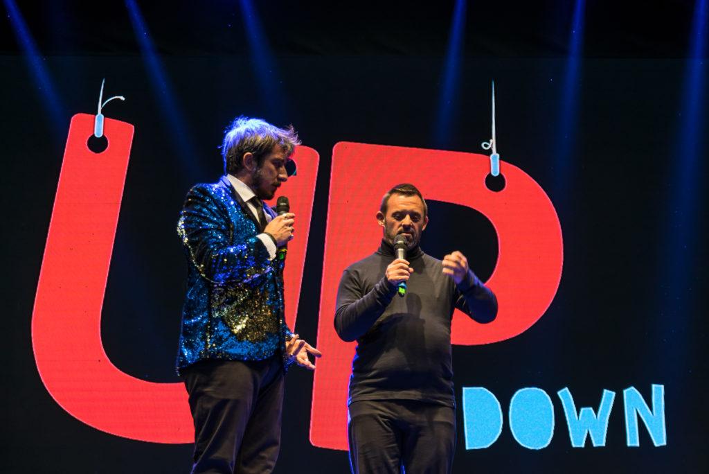 Paolo Ruffini, vestito con camicia bianca cravatta e giacca di lamè azzurra e dorata, e federico con la barba vestito di nero, dietro di loro la scritta up and down