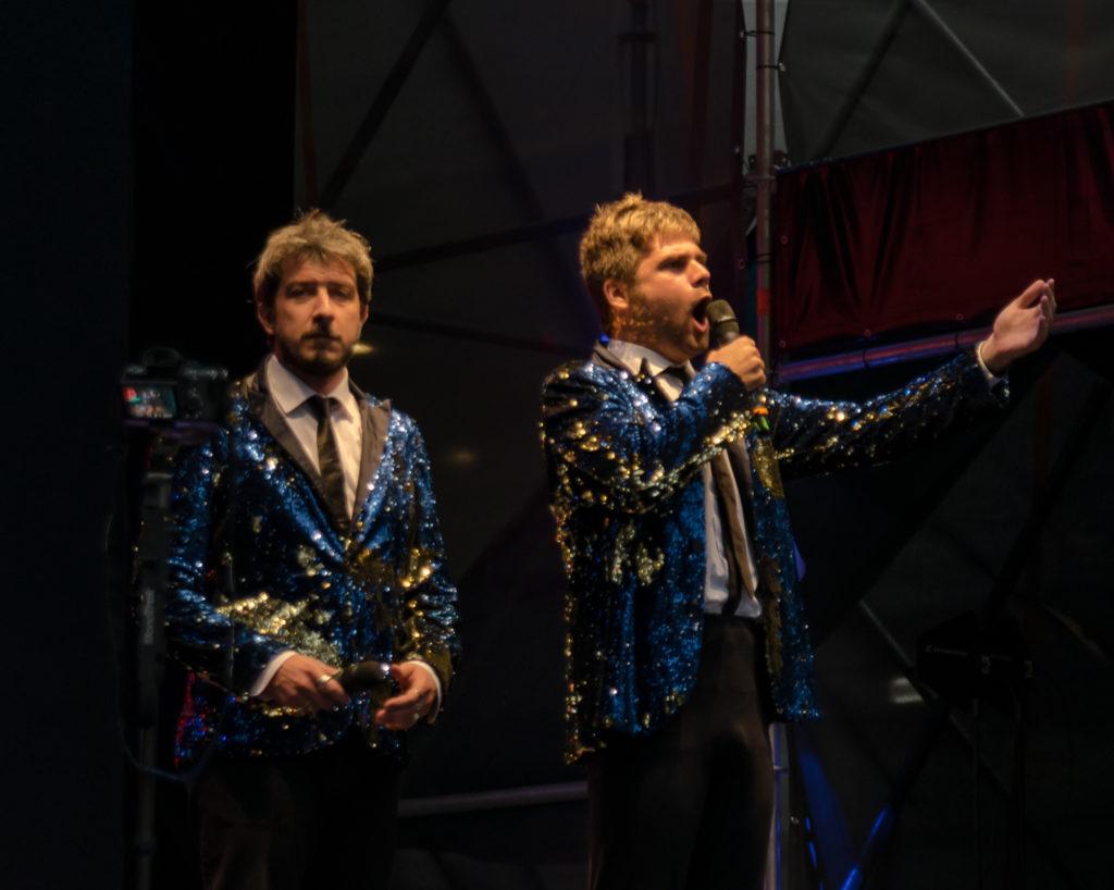 Paolo Ruffini e David insieme sul palco vestiti uguali, con la stessa camicia bianca, cravatta nera e giacca di lamè azzurra e dorata