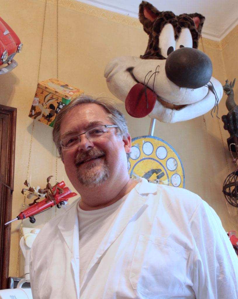 arte e medicina nell'ambulatorio del dottor ravezzani, nella foto con camice bianco, sorridente. Dietro di lui un pupazzo del gatto silvestro