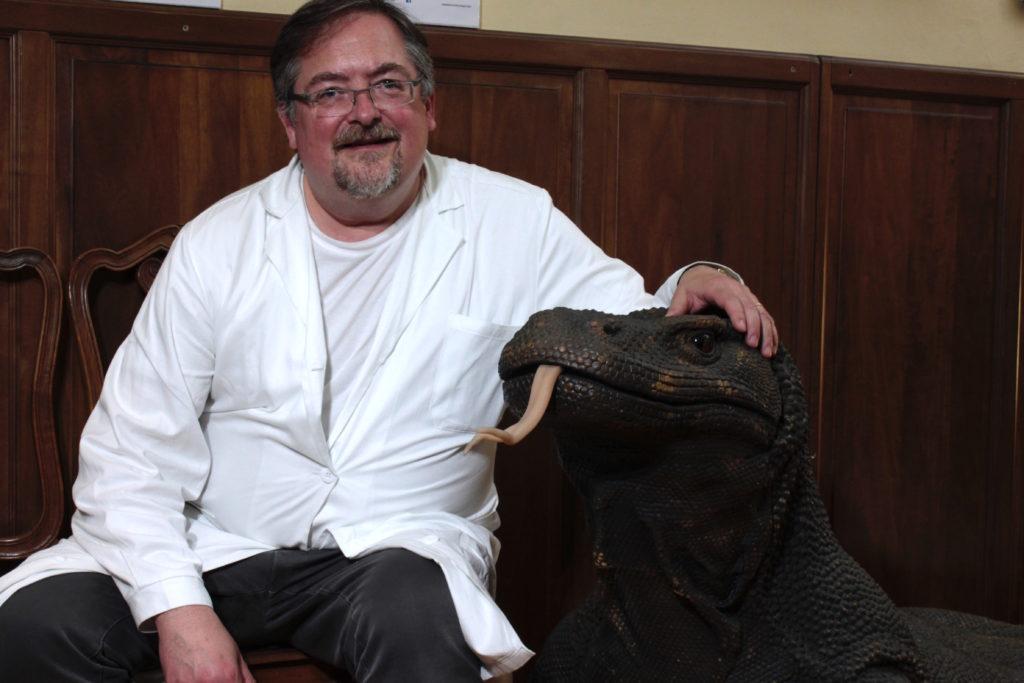 arte e medicina - il dottor ravazzani con il camice bianco seduto abbraccia un pupazzo dinosauro