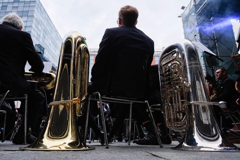 parcodora Live: due tromboni, uno dorato e l'altro color argento posizionati ai lati di una sedia  messa di schiena con un musicista (di schiena) seduto