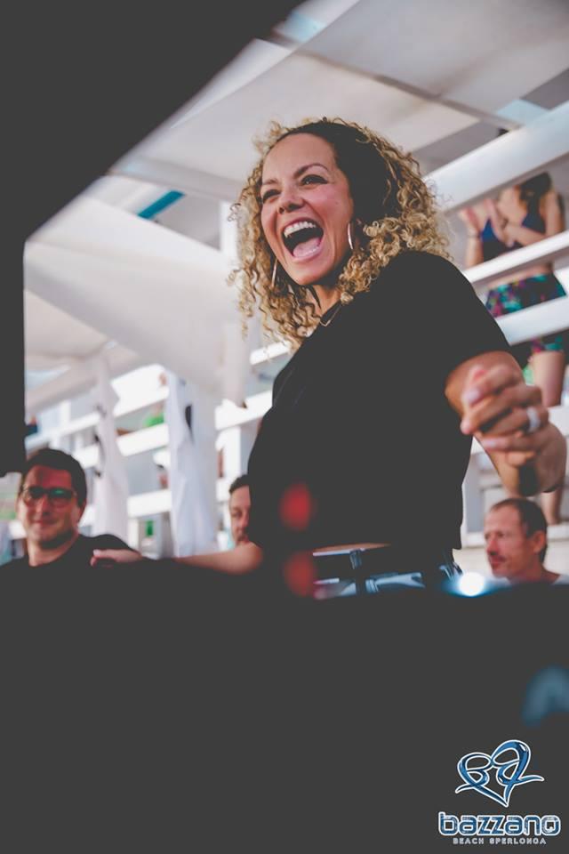 Ananè Vega ride divertita, indossa una t shirt nera. sullo sfondo del pubblico e in basso a destra il logo dei bazzano beach
