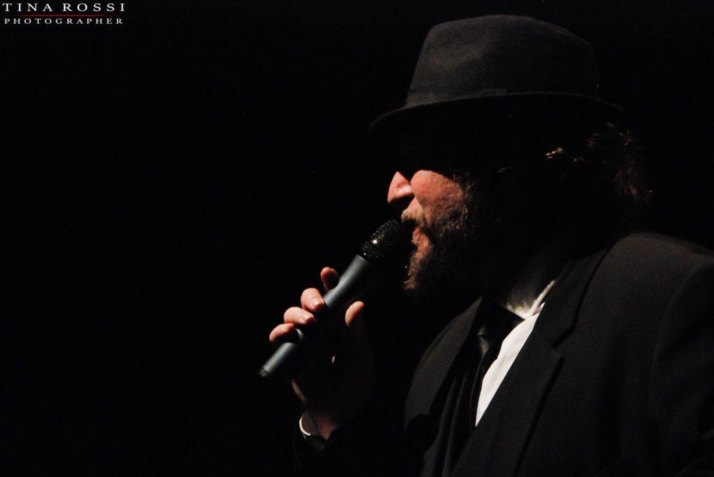 Primo piano di Diego Casale, presentatore della serata di compleanno dei Soundtruck. Diego ha il microfono in mano.