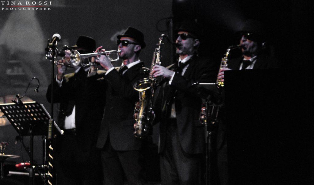 Primo piano della sezione fiati dei Soundtruck, abbigliati di nero con gli strumenti in mano
