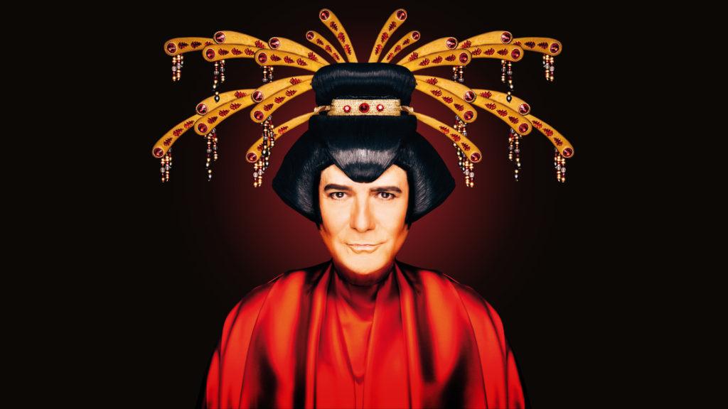 """Uno dei tanti volti di """"Mille e uno Zero"""", nella foto Renato Zero è vestito con un kimono rosso con una parrucca tipica cinese ed un copricapo che ricorda la ruota diun pavvone"""