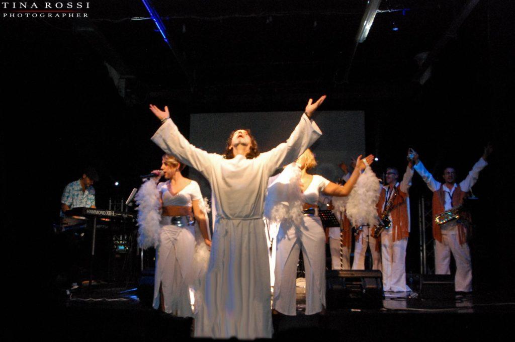 primo piano della coreografia relativa a jesus christ superstar con l'interprete di Gesù a braccia alzate