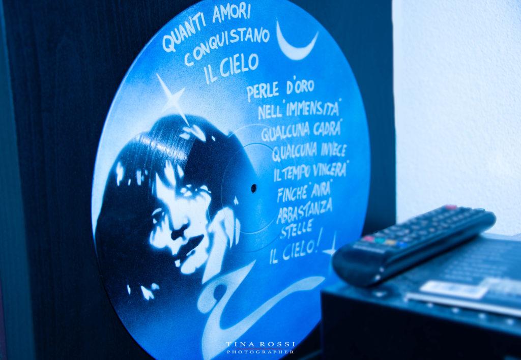 """Nella foto un vinile azzurro disegnato a mano riporta il viso di Renato Zero e una scritta tratta dal brano """"il cielo"""""""