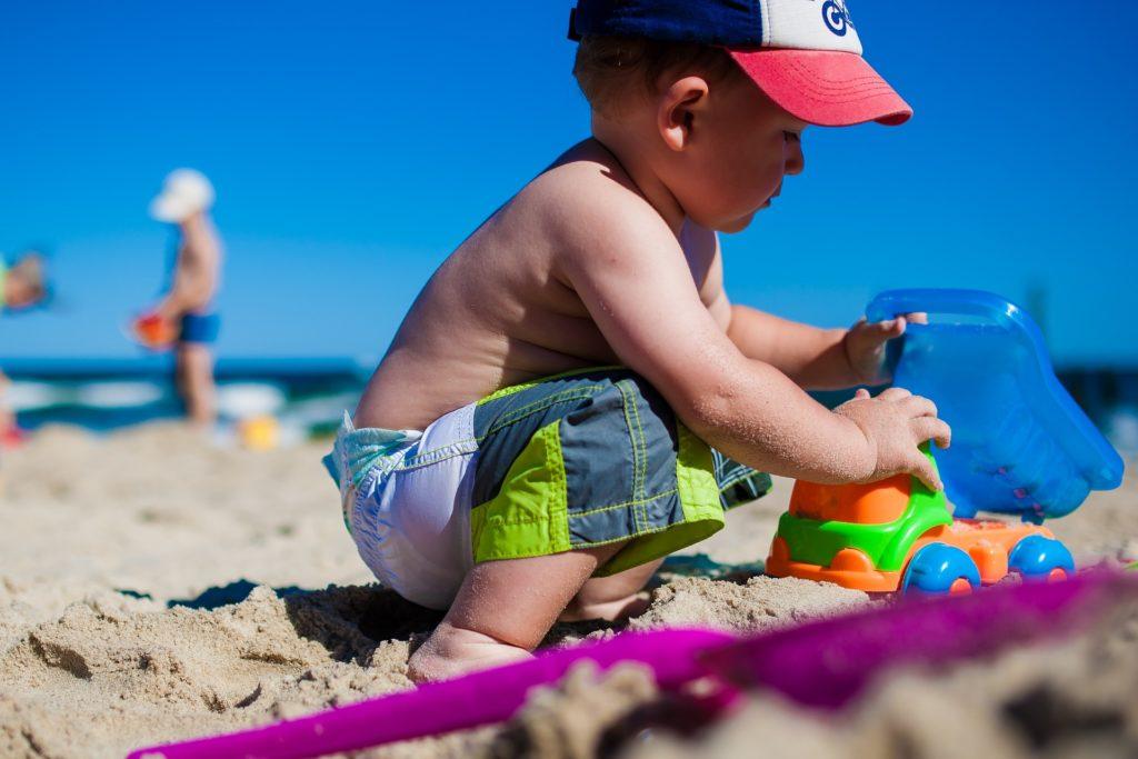 Un bambino che gioca in riva al mare con formine colorate
