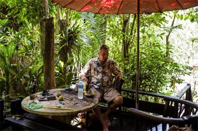 il falsario d' arte Driessen nella sua caffetteria in Thailandia, seduto su delle panche in legno, all'interno di una giungla di bamboo con tavolino pieno di colori e pennelli, vestito con camicia hawaiana
