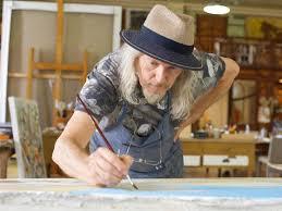 il pittore falsario d' arte Wlfgang Beltracchi mentre dipinge con pennello nella mano destra nel suo studio un quadro con colori azzurri