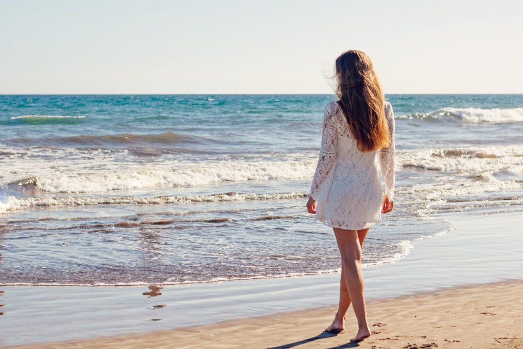 Ragazza in piedi di schiena, vestita di  bianco, che guarda il mare