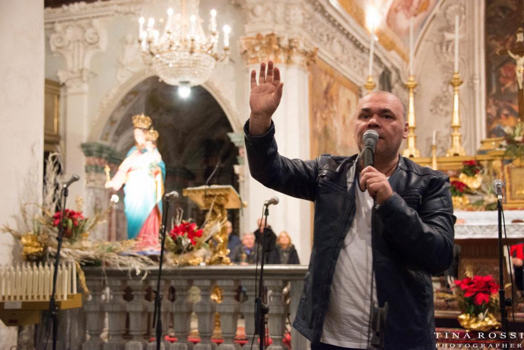 Gatto Panceri con il braccio destro alzato e il microfono nella mano sinistra sta cantando in una chiesa e sullo sfondo la statua della Madonna