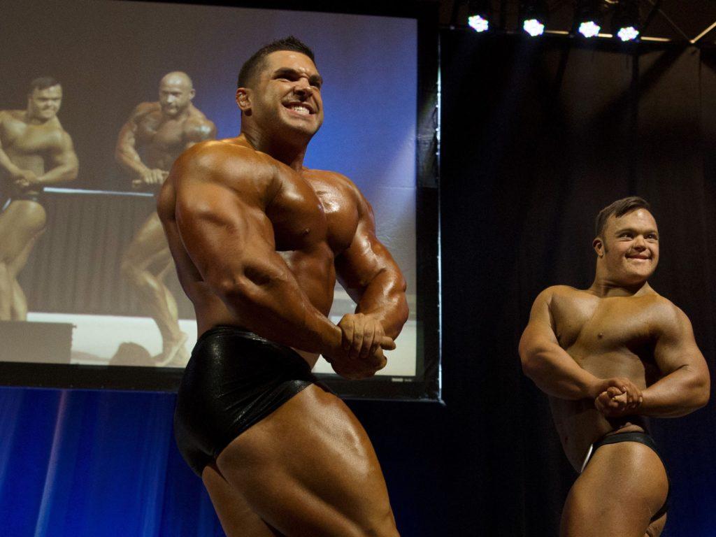 il fitness è per tutti con due bodybuilders in posa di cuiuno con sindrome di down