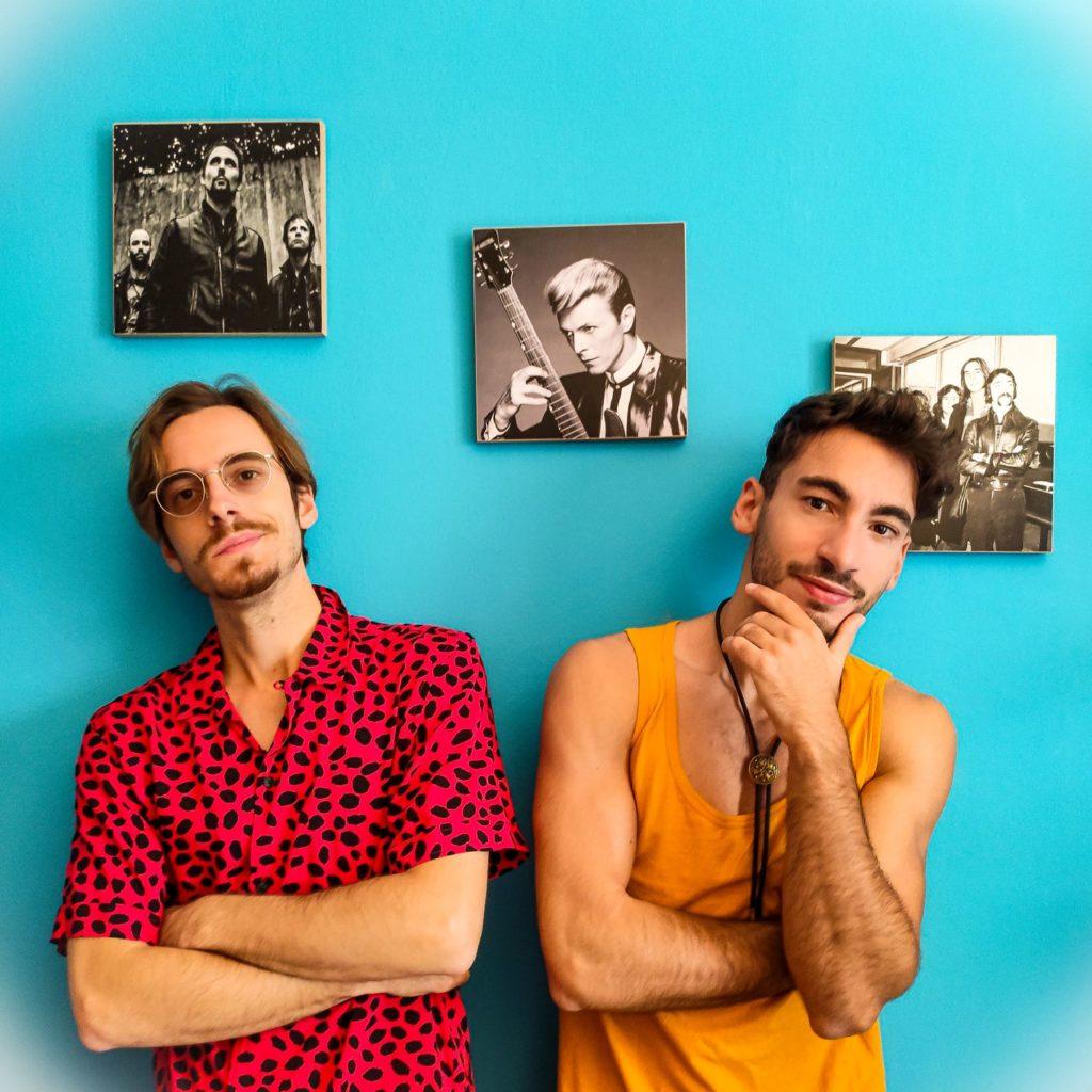 Le Tendenze: Daniele e Francesco Saibene, i cantanti de la vita di un clown.  Daniele è vestito con una camicia leopardata rossa e nera e Francesco con una canottiera gialla. Dietro di loro su una parete azzurra il quadro di David Bowie
