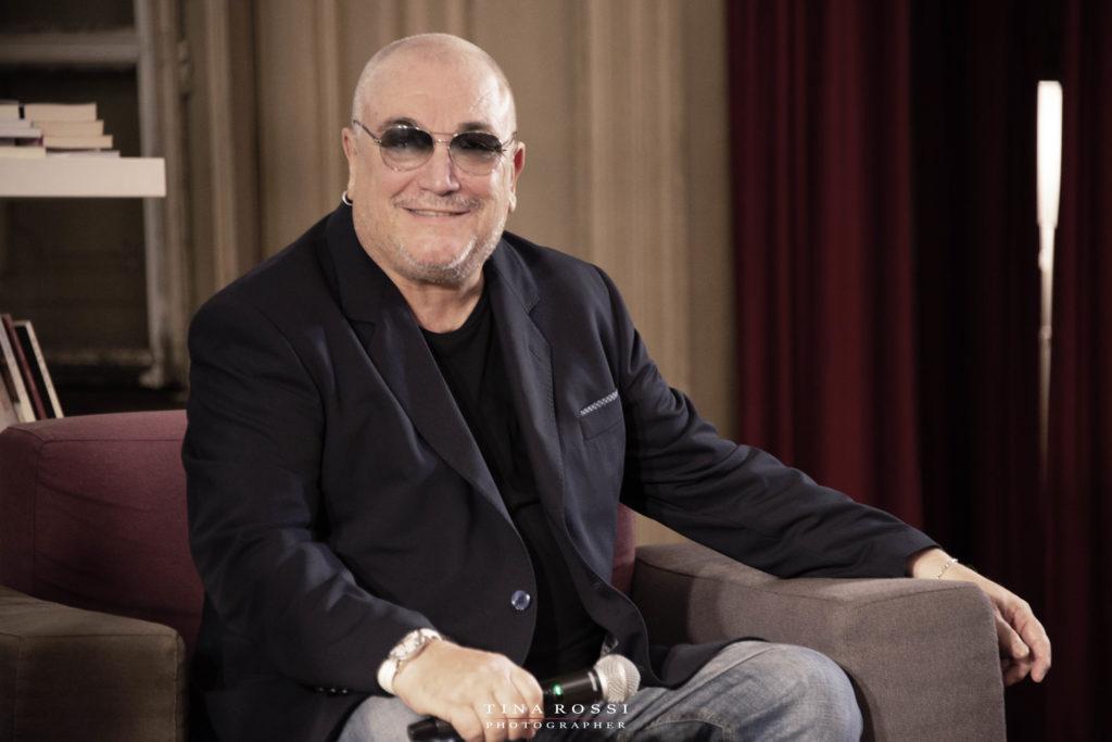 Valerio Liboni, sorridente, con giacca e maglietta scura, seduto su una poltrona rossa, parteciperà alla fiera del tartufo