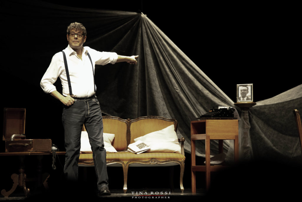 Sandro Calabrò in una scena dello zoo di vetro dove indica con il braccio sinistro la foto del padre scomparso con un divano a due posti dietro di lui e un grammofono sulla sua destra
