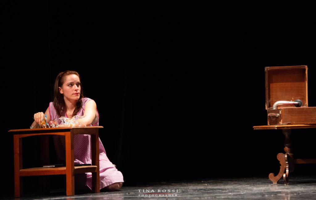 """Linda Borello in ginocchio davanti ad un tavolino con il suo """" zoo di vetro"""" e sulla destra un grammofono"""