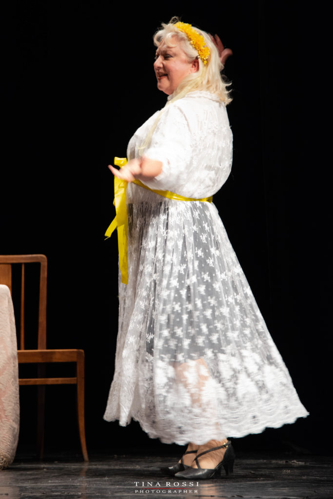 Fulvia Ruggero con una vestaglia di pizzo bianca e un nastro giallo tra i capelli biondi