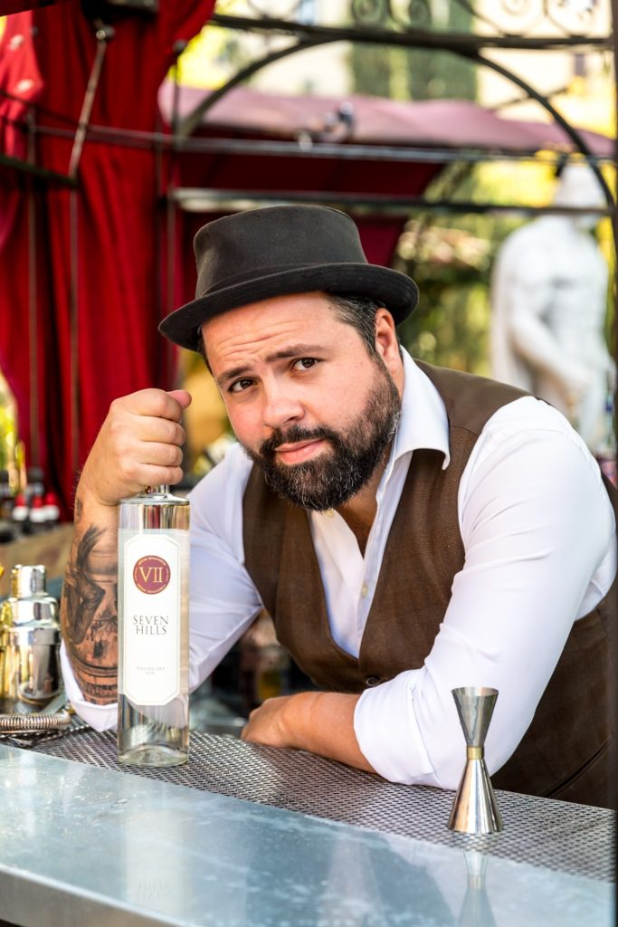 Federico Leone con un cappello , camicia bianca e gillet marrone appoggiato su un tavolo tiene in mano una bottiglia di gin con la quale preparerà la drink list