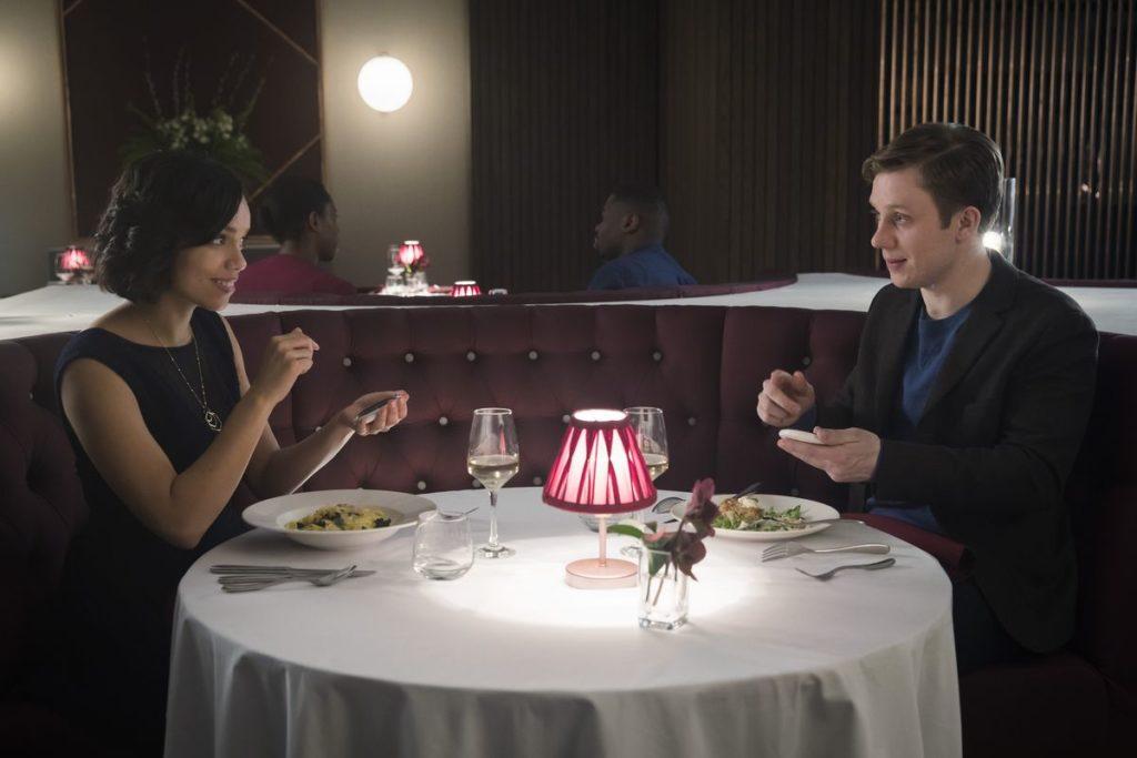 Black mirror: Una coppia seduta ad un tavolo di ristorante, rotondo, con ciascuno davanti un piatto di pasta un bicchiere di vino bianco e una lampada rossa a centro tavola, stanno sorridendosi e chiacchierano