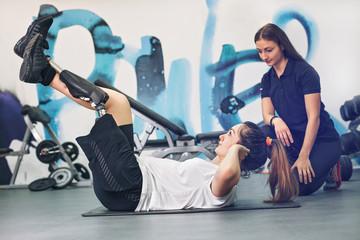 il fitness è per tutti una ragazza senza un arto si allena per terra in palestra e con lei la sua personal trainer