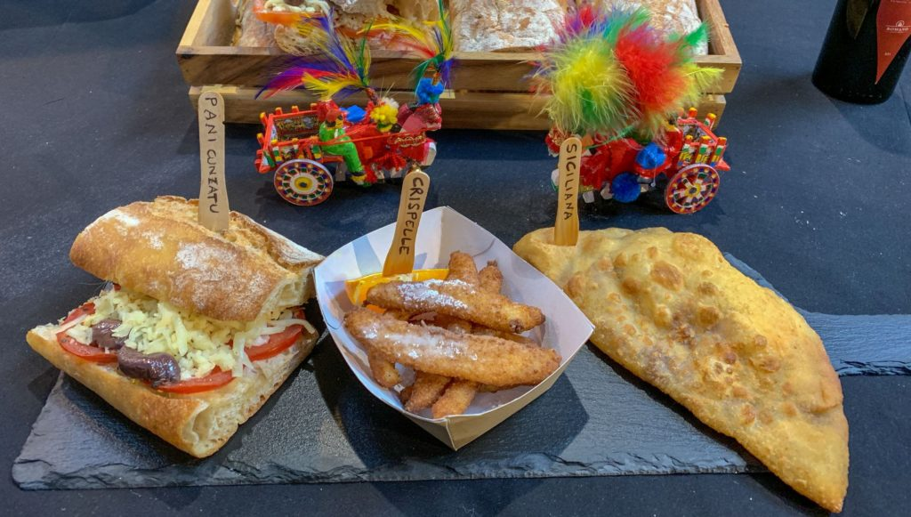 Sicily Fest London con un paniee quadrato di prodotti tipici siciliani, il classico carrretto e delle vaschette con del cibo
