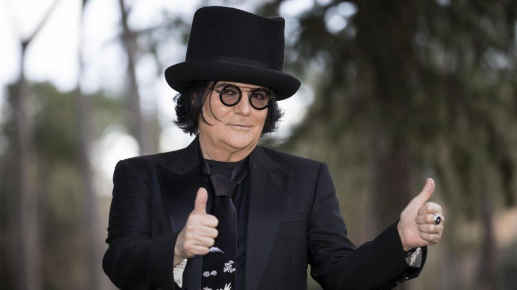 Zero il Folle a Roma con cappello, occhiali neri e abito nero con cravatta con i pollici all'insu