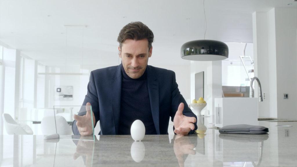 Black Mirror: un uomo seduto ad n tavolo da cucina con le mani appoggiate e aperte osserva un uovo
