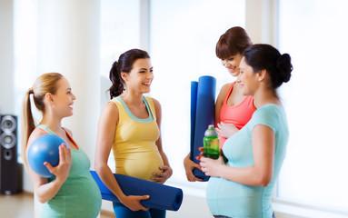quattro donne in gravidanza con dei tubi d'allenamento in mano, chiacchierano in palestra