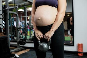 una donna con il pancione della gravidanza in primo piano, vestita con top nero e pantaloni neri tiene in mano un peso da palestra