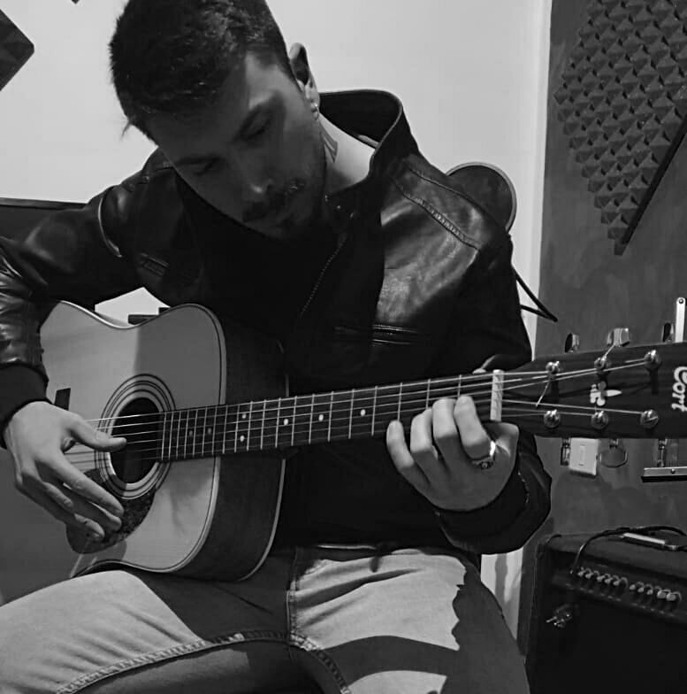 Francesco Setta mentre suona la chitarra classica seduto, con giubbottonero. Foto in bianco e nero