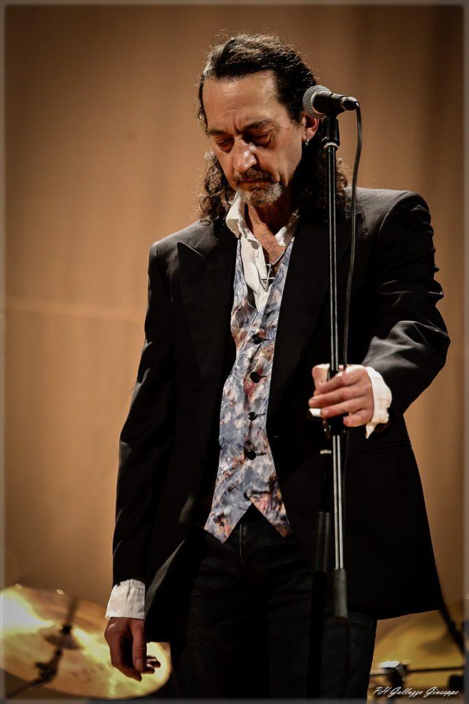 Il frontman dei Rudi Trudi Dario Dell'ara canta America con giacca nera e camicia a fiori con la mano sinistra tiene l asta del microfono