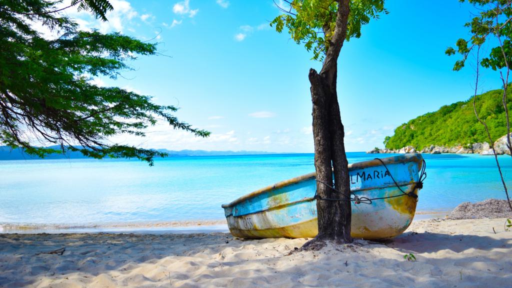 paesaggio caraibica del Costa Rica, spiaggia di sabbia bianca con una barca abbandonata arenata legata a un albero
