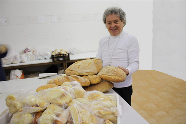 Don Adriano aiuta i poveri con delle pagnotte di pane