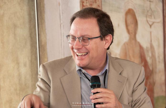Il proprietario di GeaWay viaggi, Enzo Toniutto sorridente e con giacca beige, occhiali da vista e microfono in mano