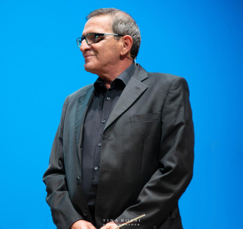 Giorgio Bolognese con vestito scuro e bachetta da direttore di orchestra in mano, presenta variety for casa giglio