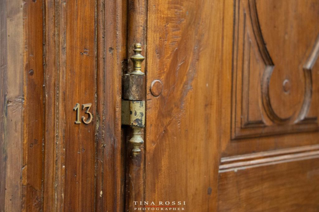 """la porta di uno degli armadi della memoria con in primo piano la cerniera della porta e il numero """"13"""""""