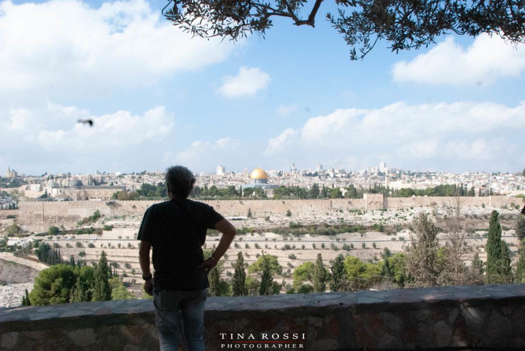 un uomo girato di spalle che guarda dalla collina del getsemani la città di gerusalemme