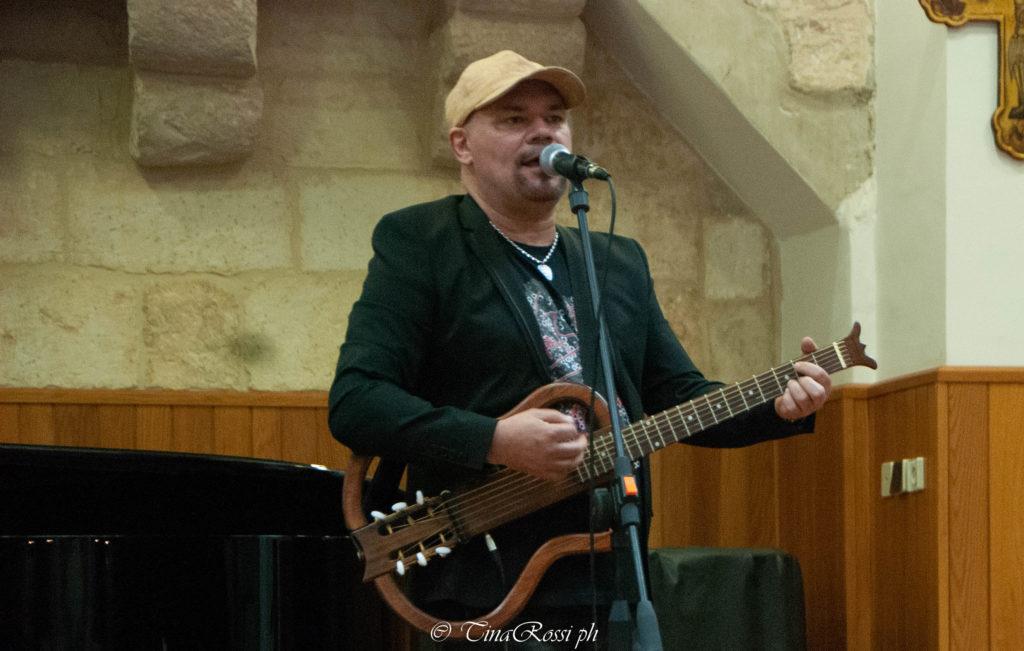 """Gatto Panceri con cappellino in testa e chitarra in mano canta davanti aun microfono """"grazie per la gioia"""""""