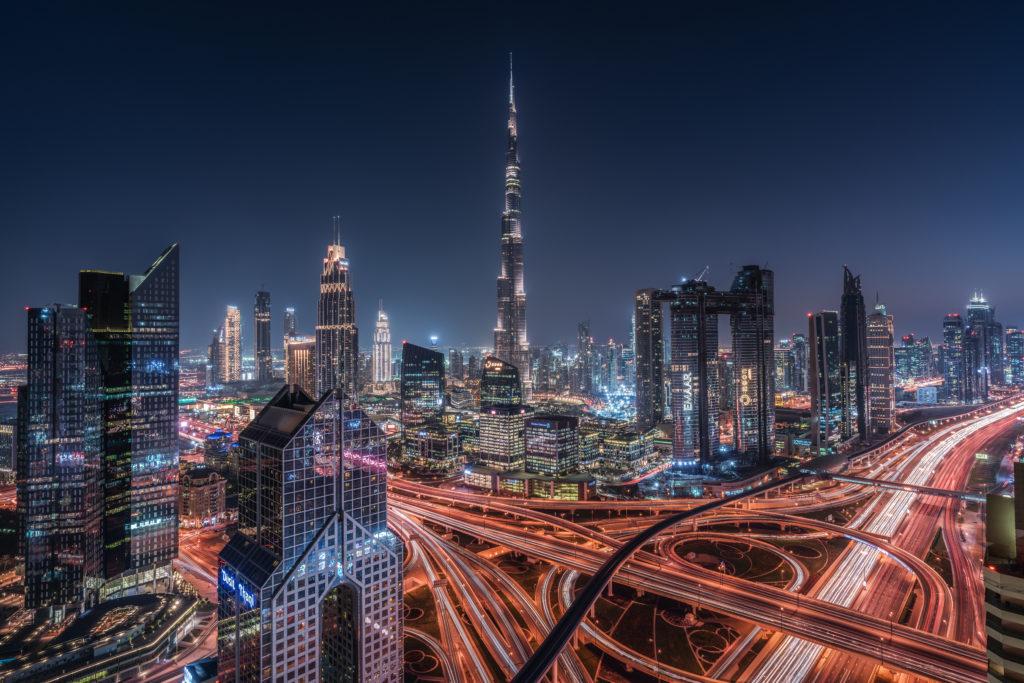 una veduta notturna della città di Dubai grattacieli illuminati e le strade che si aggrovigliano sembrano linee rosse